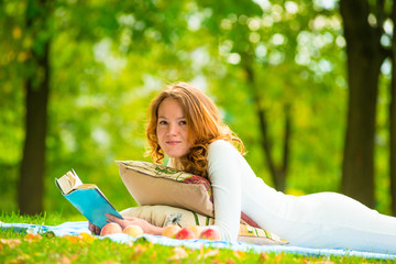 portrait of a beautiful student in a summer park with a book
