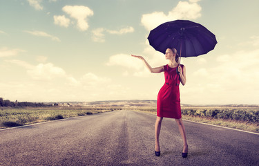 Stylish female with umbrella standing on highway at sunny day