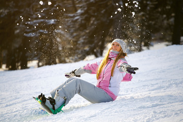 Happy smiling girl with lifted hands  on snowboard