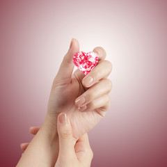 hand holding 3d red heart shape of diamond
