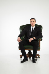 Male businessman sitting on a green leather chair on a white bac