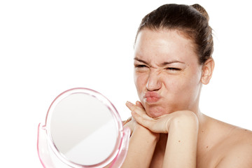 young woman making faces on the mirror