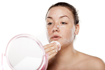 young woman cleans her face with cream