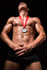 Muscular sportsmen with medal on his chest