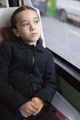 Niña pensativa en el autobús