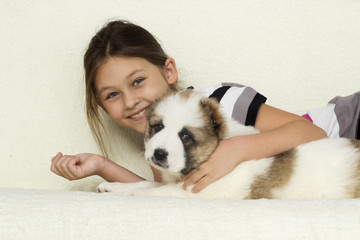 child, gently hugging a puppy