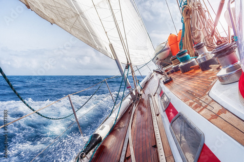 Poster sail boat navigating on the waves