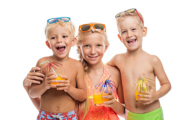 Three happy kids in a swimsuit standing together, isolated on wh