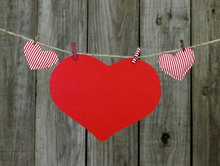 Red hearts hanging on clothesline by wood fence