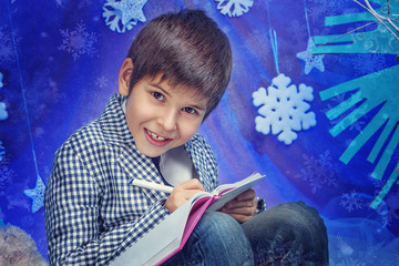 Winter Fashion. Portrait of adorable boy in jacket with book in