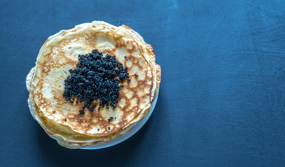 Pile of crepes with black caviar