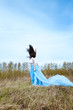 Beautiful woman in blue long dress with flying fabric