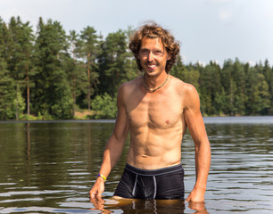 Smiling muscular man comes out of lake water