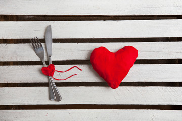 Concept image for Valentine dining, fork, spoon and red heart