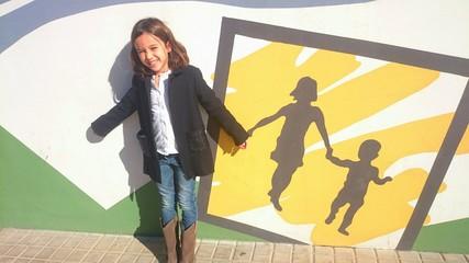 Niña dando la mano a graffiti de madre