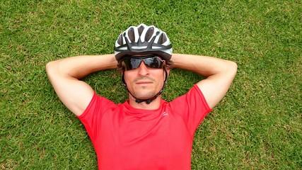 Ciclista tumbado de cara al cielo