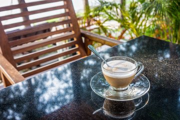 A glass cup of coffee on granite stone table