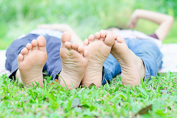 Little boy lay on grass show feet in the park