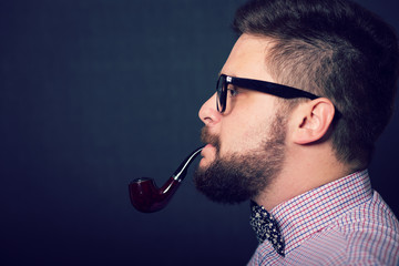 Young bearded hipster man smoking pipe