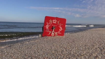 antique red broken clock face dial on summer sea resort beach