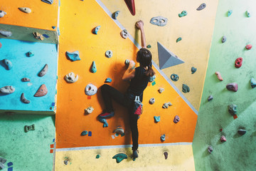 Girl climbing up on practice wall
