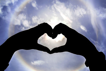 silhouette hand in heart shape with sun halo background
