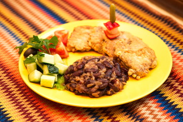 the beef tongue in batter with beans on the yellow plate