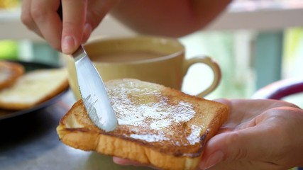 Female Hands Making Toast with Butter and Jam. Breakfast.