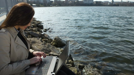 Businesswoman with laptop sitting on a beach in the sea coast