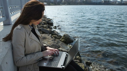 Happy business woman with a laptop sitting on beach