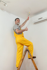 Worker painting ceiling in room with paint roller and gesturing