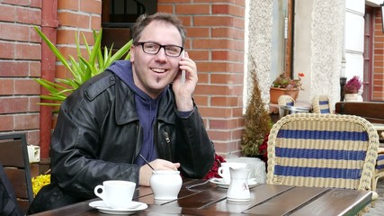 Smiling man in glasses is talking on a mobile phone