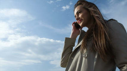 Young girl with phone against blue sky