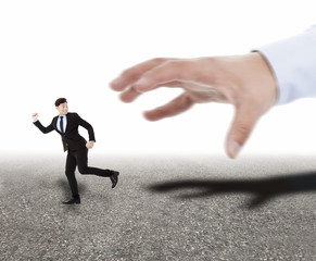 large hand trying to catch running businessman