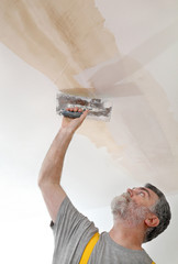 Worker repairing plaster at ceiling with trowel