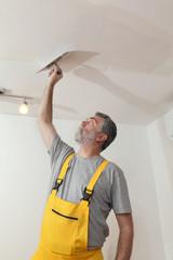 Caucasian worker repairing plaster at ceiling with trowel tool