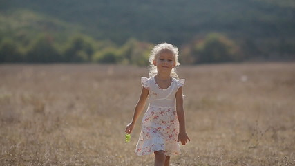 Thoughtful little girl goes on meadow in slow motion