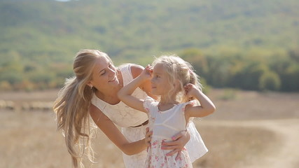 Young beautiful mother kissing little daughter and circling her