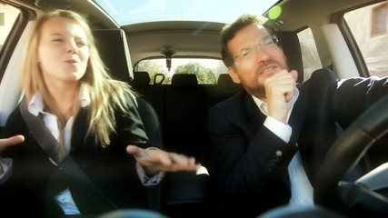 Happy business couple singing in car