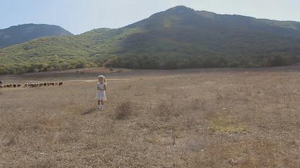 Little girl running across the field where flock of sheep