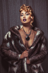 Fashionable blonde woman with make up looking at camera in fur c