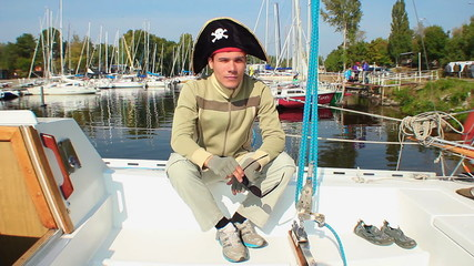 Young adult funny pirate hat on, yachts in marina, recreation