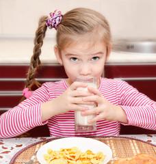 Cute little girl having breakfast drinking milk