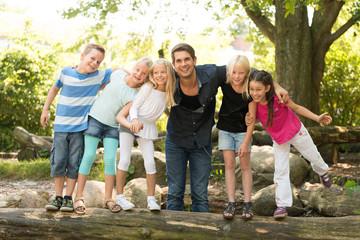 Kinder mit Lehrer auf dem Spielplatz
