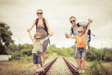 Happy family walking on the railway at the day time.