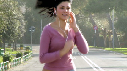 Gorgeous woman jogging on street listening music