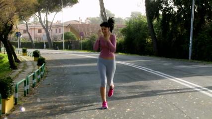 Beautiful woman listening music while running on street