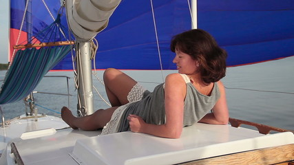 Pretty girl relaxing on yacht, smiling flirtatiously at camera