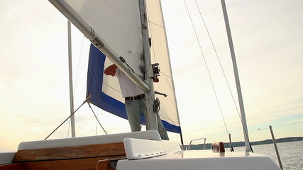 Senior man raising the mainsail on boat, yachting, traveling