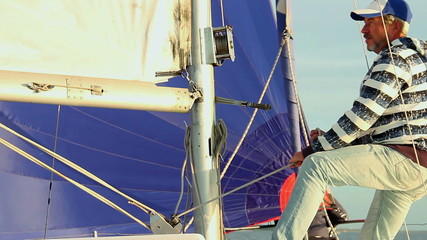 Man pulling rope, securing the mainsail on sailboat, yacht